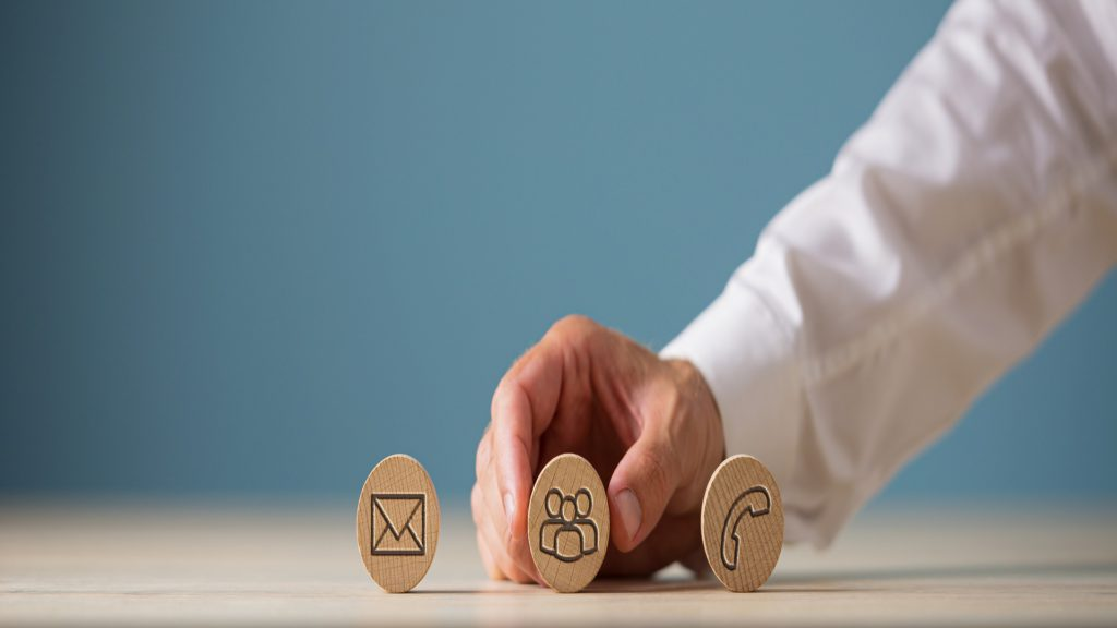 Wide view image of customer service representative placing three wooden cut circles with contact and information icons on them in a row.