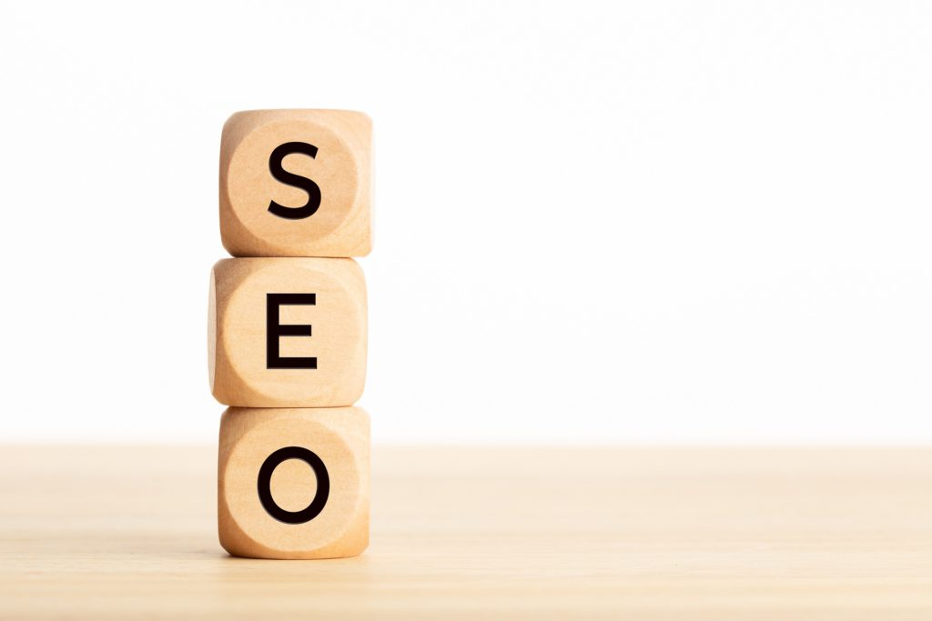 SEO word in wooden blocks on table. White background Copy space